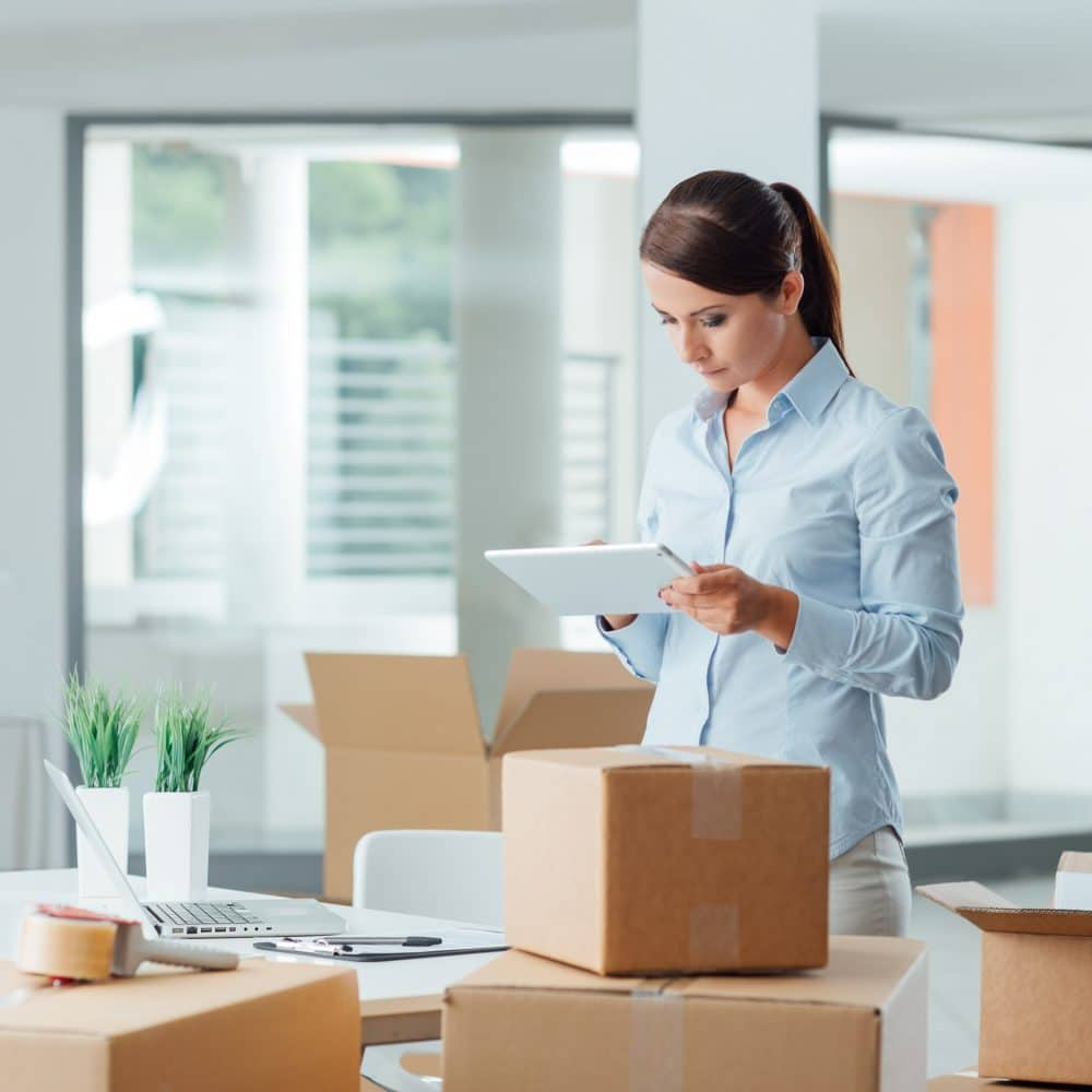 Confident business woman moving in her new office and using a digital tablet, she is surrounded by cardboard boxes